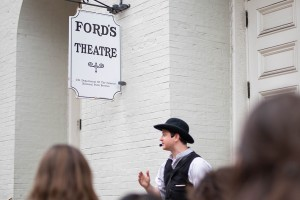 Actor Chris Stinson, dressed as Detective McDevitt, leads a tour on the outdoor steps of Ford's Theatre.
