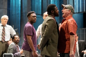 : Four men stand in a jury room, where other jurors are seated. A white man in a ballcap yells in the face of a black man with whom he disagrees.