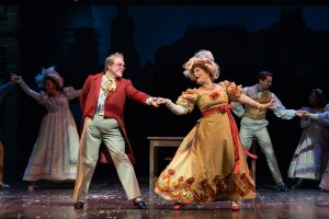 A portly gentleman wearing Victorian-style clothes including a spritely red coat dances with a red-headed woman wearing a Victorian-style dress. Other dancing couples can be seen in the background.