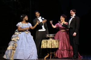 Two Victorian couples in fancy dresses and suits stand raising a toast around a silver punch bowl.