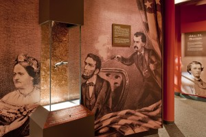In the middle of a tall glass display case, a small silver gun appears to float in mid-air. Behind the case is a wall-sized drawing of John Wilkes Booth shooting Abraham Lincoln.