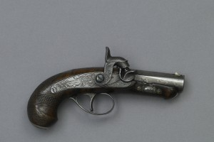 "Side view of small pistol, with wooden, rounded handle, metal trigger, and metal shaft. Inscription says ""Deringer, Phila.,"" representing manufacturer."