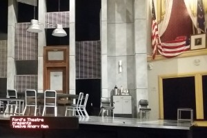 "On the lip of the Ford's Theatre stage sits a thin horizontal screen on which a pre-perfomance message reads ""Ford's Theatre presents 'Twelve Angry Men'."" This device is used for captioned performances at Ford's Theatre."