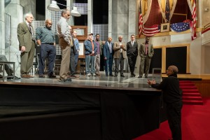 Twelve Angry Men director Sheldon Epps stands off stage in historic Ford's Theatre, addressing his cast who are gathered on the set. Behind Epps and just off the right of the photo is the Presidential Box where President Abraham Lincoln sat when attending