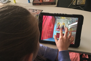 A girl uses a tablet computer to access a virtual tour of Ford's Theatre stage.