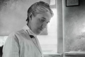 Henrietta Swan Leavitt sits at a desk, pencil in hand, writing in a large notebook at the Harvard Observatory.
