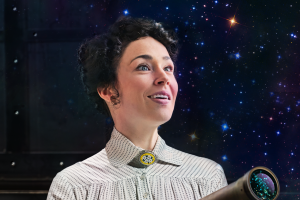 A woman in early 20th-century dress stares up to the sky with hope and wonder. She has a telescope and is standing in front of a star-studded background.