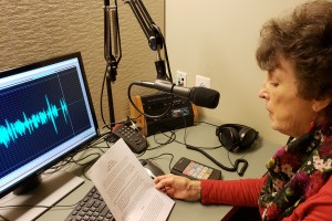 "A woman sits behind a microphone and computer in a digital voice recording studio and reads aloud a script of welcome remarks for the Ford's Theatre stage production of ""The Wiz."""