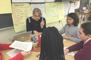 A teacher sits at a classroom table talking with four middle-school students.