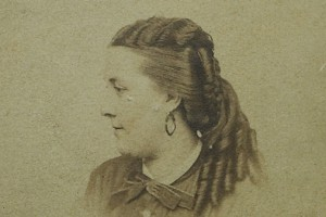 Photo profile of a woman with traditional 1860s curls and earrings.