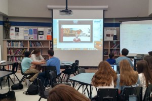 Students watch a teacher who is a screen in front of them.
