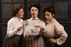 Three women wearing collared Victorian blouses and high-waisted skirts stand together. The woman in the middle is holding a photographic plate on which an image of stars in the sky is shown.