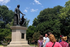 A group of teachers in front of a statue featuring President Abraham Lincoln, standing, and a shirtless African American man, Archer Alexander, kneeling.