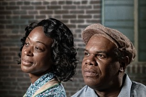 "Actors playing August Wilson's characters Rose and Troy from the play ""Fences"" sit together in their 1950s costumes. Rose wears a tan apron over a short-sleeved house dress that is patterned with small blue flowers. Troy wears khakis, a short-sleeved blue"