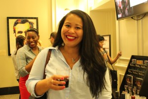 A young woman stands with a glass of wine in the lobby of Ford's Theatre and smiles at the camera. She is attending a Generation Abe event at Ford's Theatre.