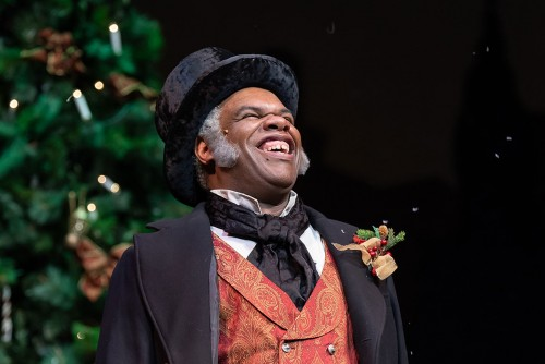 A smiling man in Victorian-style clothes and a top hat stands in front of a Christmas tree.
