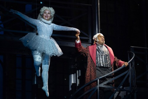 A joyful spirit flies through the air in a sparkling, long-sleeved unitard and matching tutu. She grasps the hand of Ebenezer Scrooge and the two glide upward.