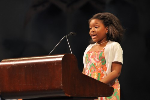 A young student stands a podium