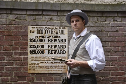 An actor portrays Detective James McDevitt standing next to a wanted poster for Booth and his conspirators.