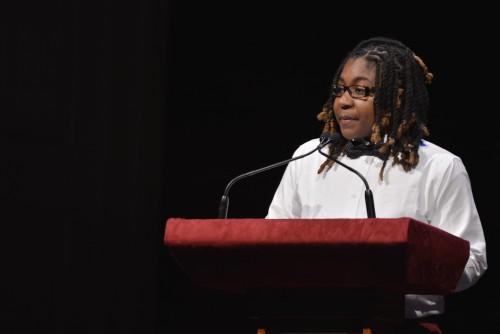 A student stands at a podium giving a speech.