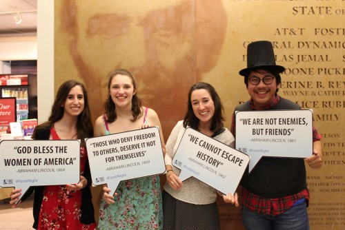 A group of young people wear top hats and hold famous quotes  by Abraham Lincoln.