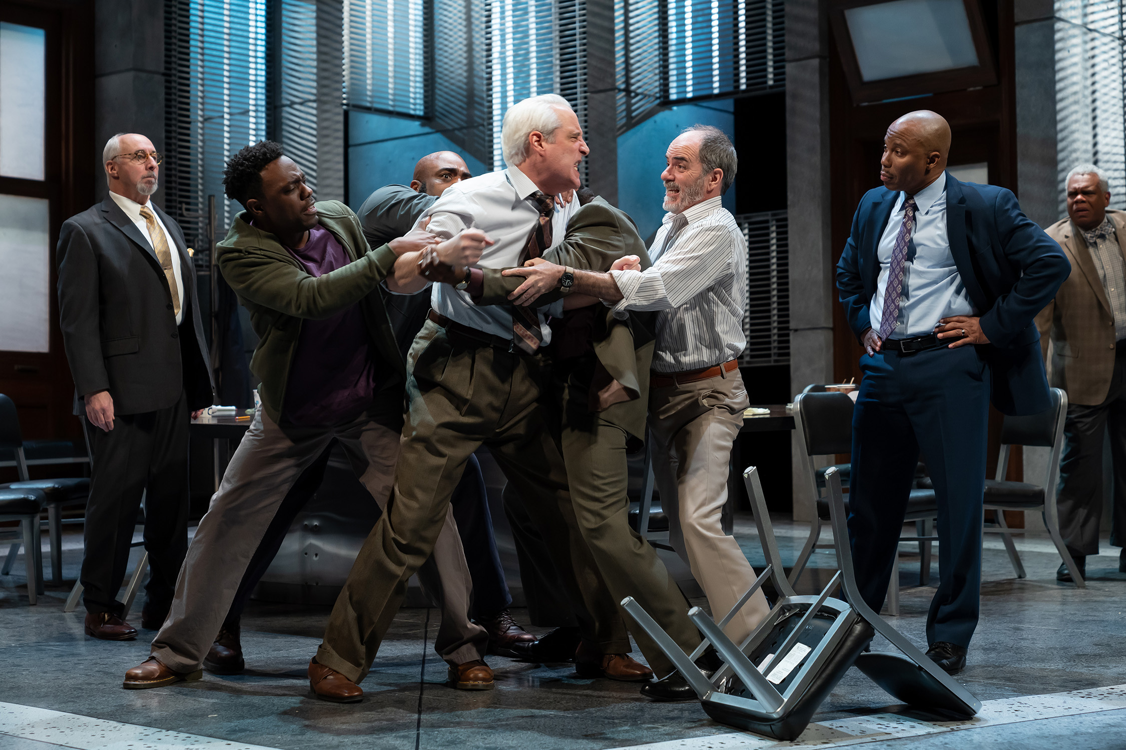 Four men physically restrain an angry man who lunges with fists clenched toward another man in a jury room. Image is from the Ford's Theatre 2019 production of Twelve Angry Men, directed by Sheldon Epps. Photo by Scott Suchman.