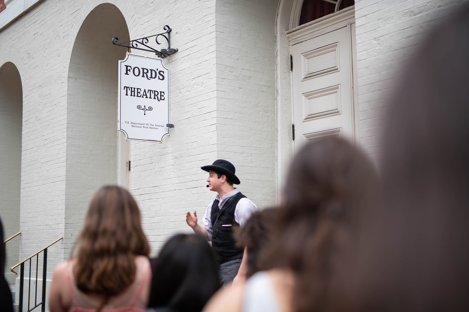 A group of young adults outside of Ford's Theatre watch a guide dressed as 1860s Washington Detective James McDevitt.