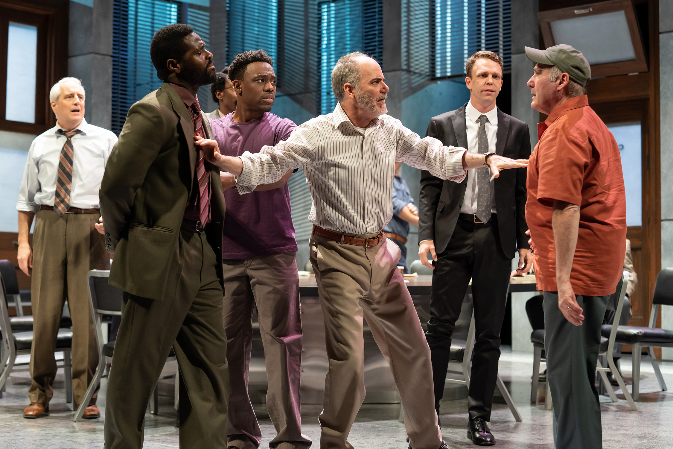 Six men stand in a jury room as heated words are exchanged between two jurors (actors Lawrence Redmond and Bueka Uwemedimo). A foreman (actor Eric Hissom) stands between the two men, attempting to deescalate the flight. Image is from the Ford's Theatre 2019 production of Twelve Angry Men, directed by Sheldon Epps. Photo by Scott Suchman.