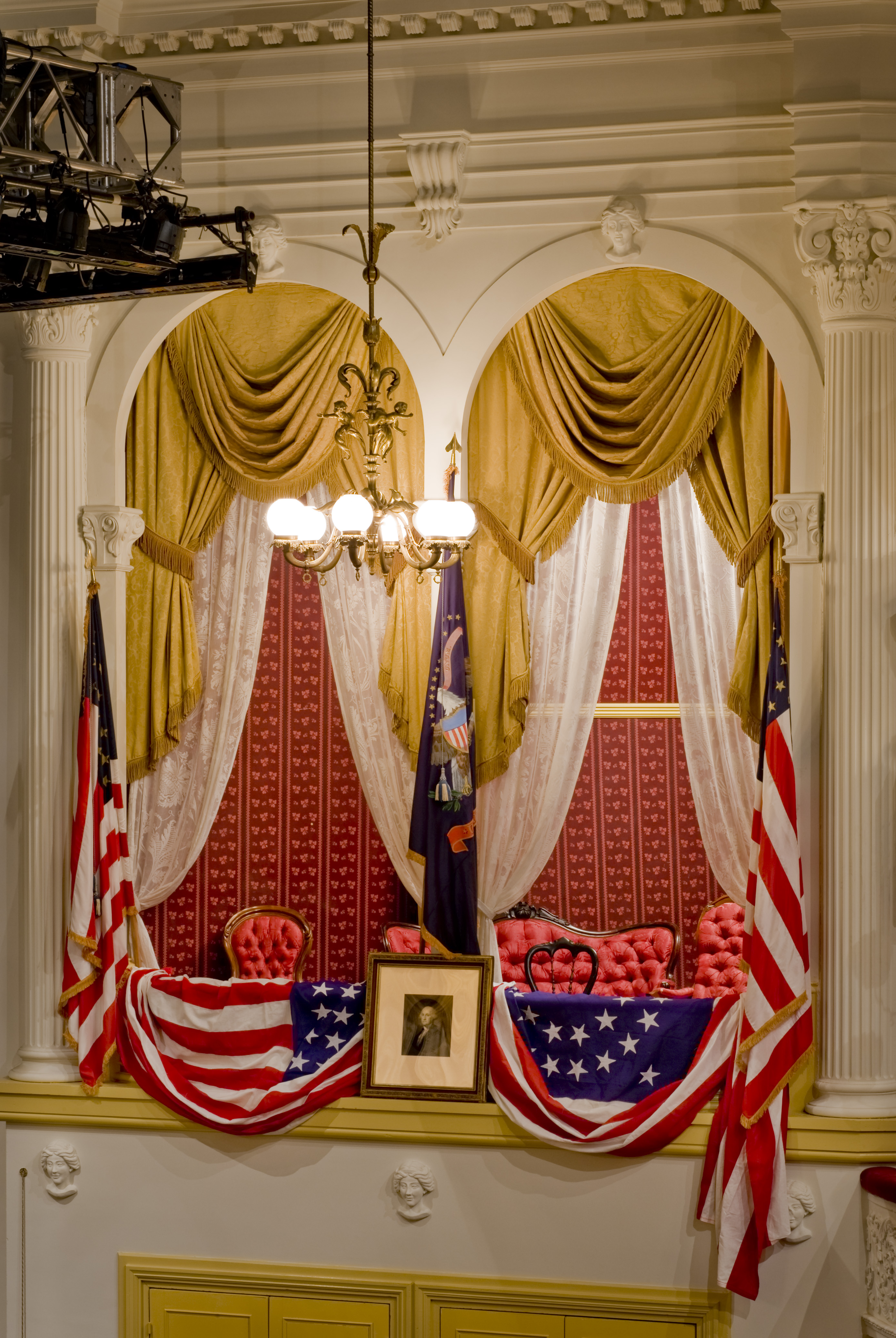 The President's Box at Ford's Theatre with American flags on either side, a picture of George Washington in the center and American flag bunting draped over the box. The interior of the box has red patterned wallpaper and red upholstered chairs and a couch. The box is framed by gold curtains with white lace curtains underneath them.