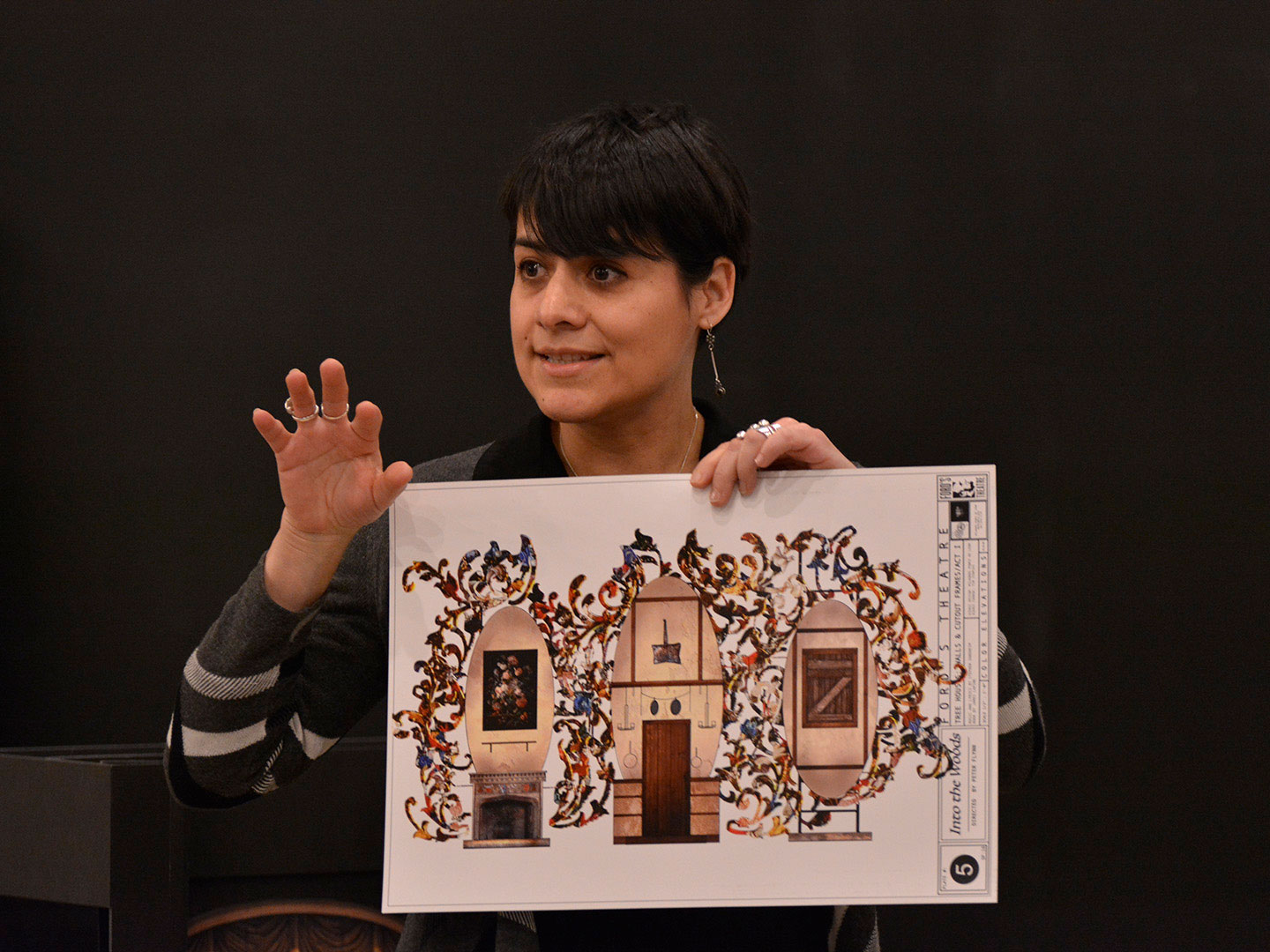 """A female scenic designer holds up a rendering of the set for a stage production of 'Into the Woods"""" at Ford's Theatre."""