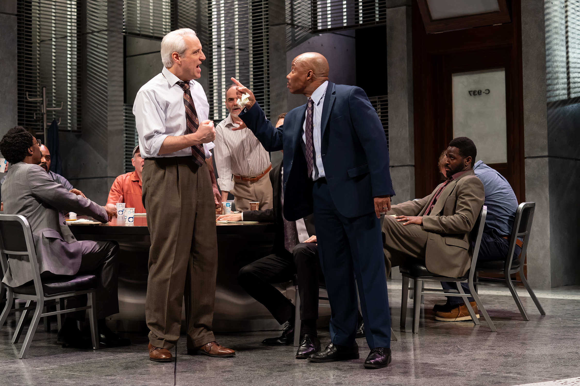 Two jurors (actors Michael Russotto and Erik King) stand, exchanging angry words in a deliberation room. Around them, seven other seated jurors sit with surprised faces. Image is from the Ford's Theatre 2019 production of Twelve Angry Men, directed by Sheldon Epps. Photo by Scott Suchman