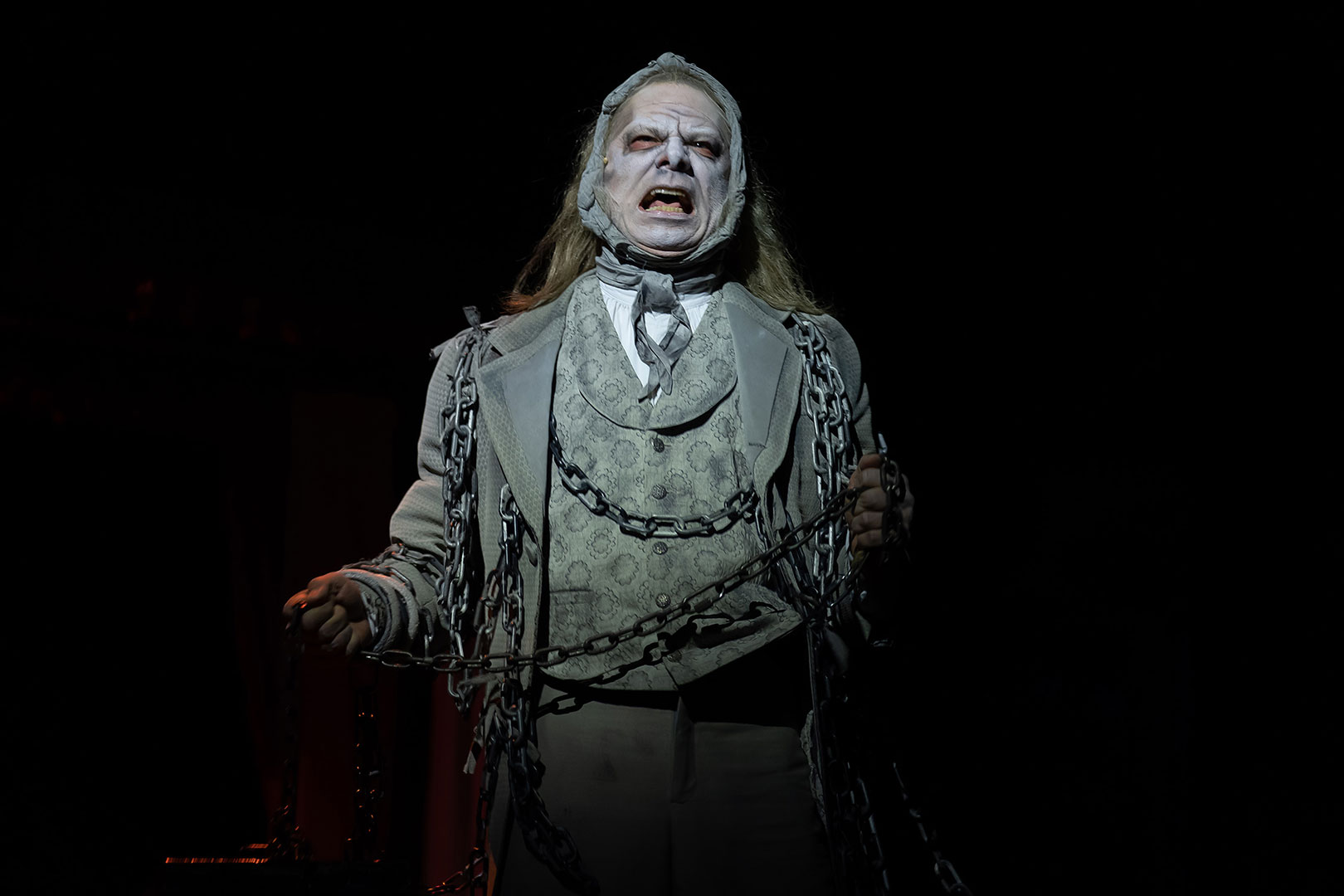 A man with a ghostly-white face and blackened eyes shouts. He wears a nice three-piece Victorian suit, but is wrapped in chains and the suit is grayed out in a ghostly fashion.