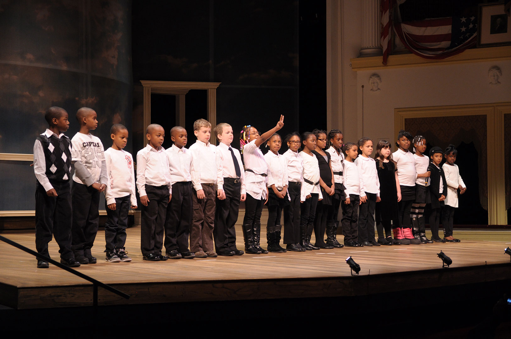 20 fourth graders stand on the stage at Ford's Theatre wearing white tops and black pants. They are reciting a historic speech for the Lincoln Oratory Festival (2012).