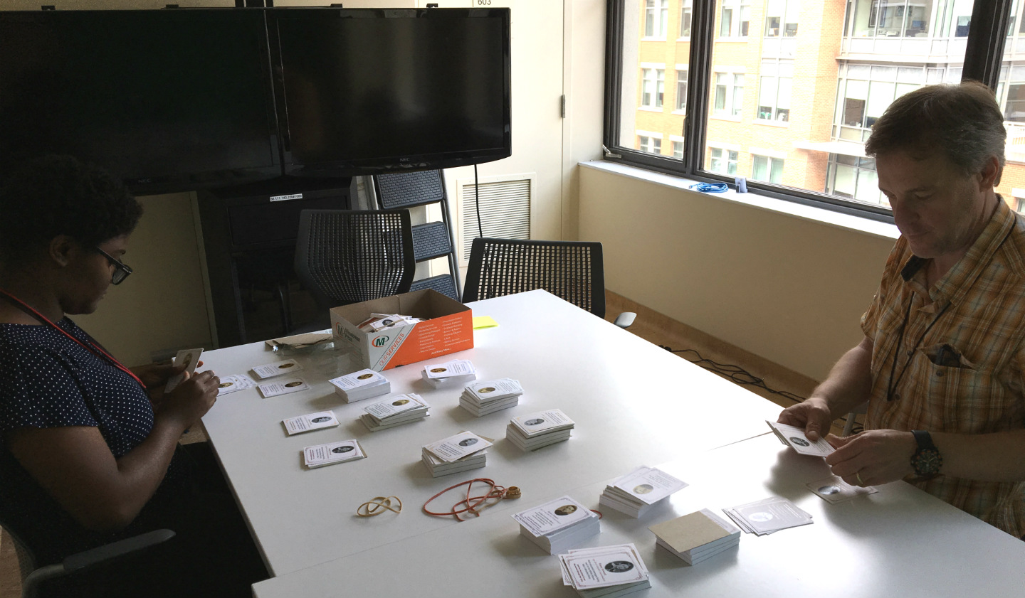 "two people sit at a large table sorting cards with different historical characters on them. The ""Character Cards"" would be handed out to visitors during this prototyping project."