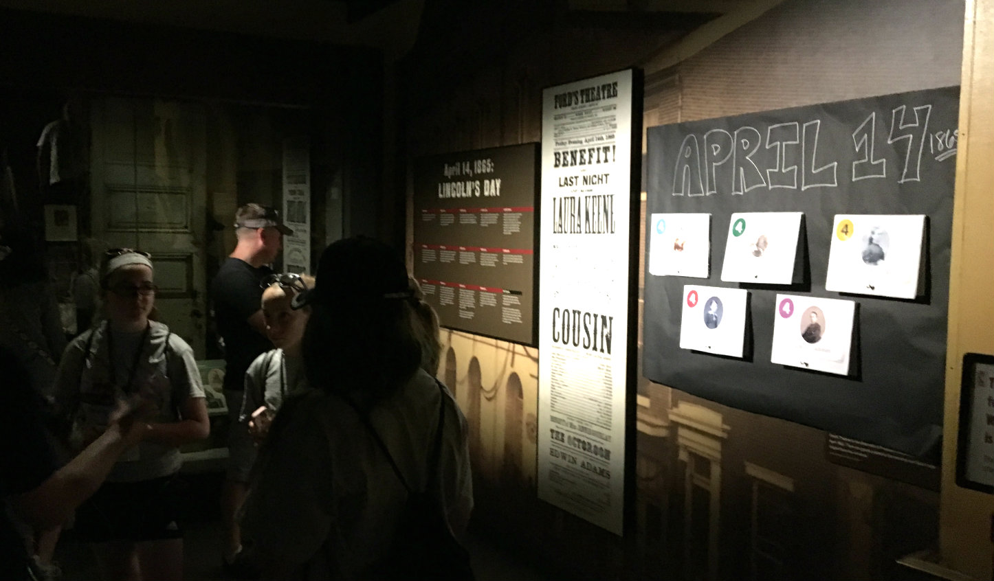 "Within the museum at Ford's Theatre, a makeshift exhibit panel reading ""April 14, 1865"" is posted on the wall. The poster features five headshots of historical characters, each of which can be flipped up to reveal details of that person's connection to the Lincoln assassination."