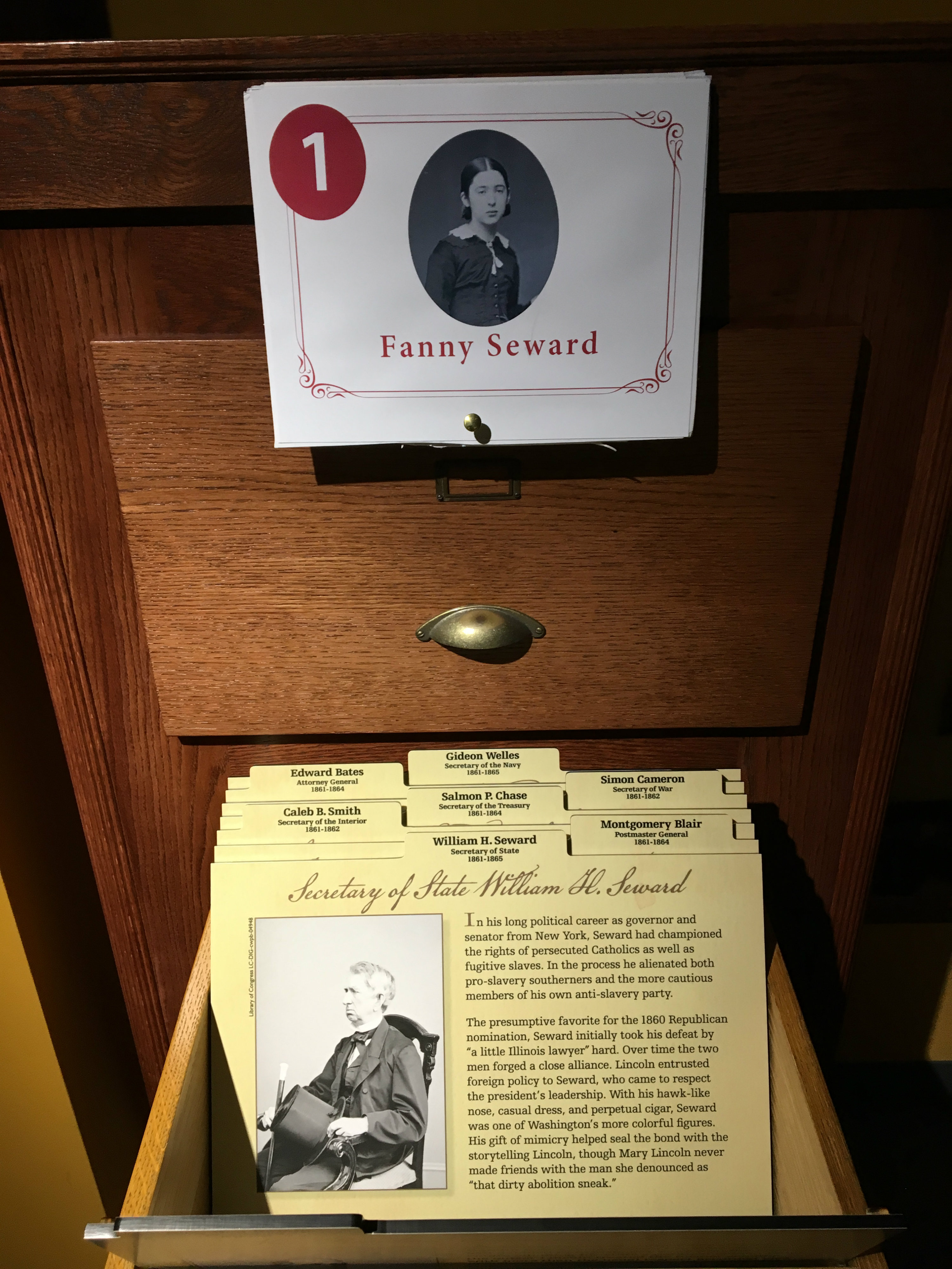 Above a cabinet in the Ford's Theatre Museum (where visitors can flip through information cards about President Lincoln's Cabinet members), is taped a black and white historical image of a young woman named Fanny Seward. The photo can be flipped up to open and reveal information about Ms. Seward (not shown).