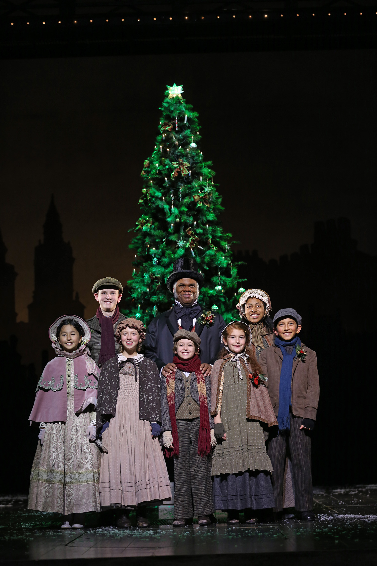 A smiling man in Victorian-style clothes and a top hat stands with a group of children, also in Victorian-style clothing, in front a large Christmas tree.