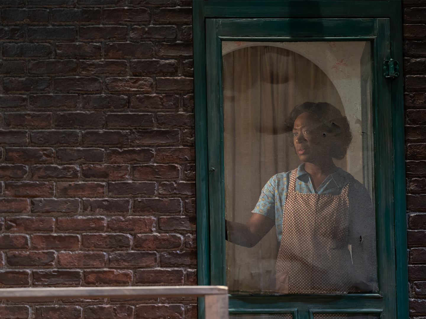 A woman stands inside the screen door of her 1950s row home, peering out into the yard. She wears a short-sleeved blue dress covered by a brown and white apron.
