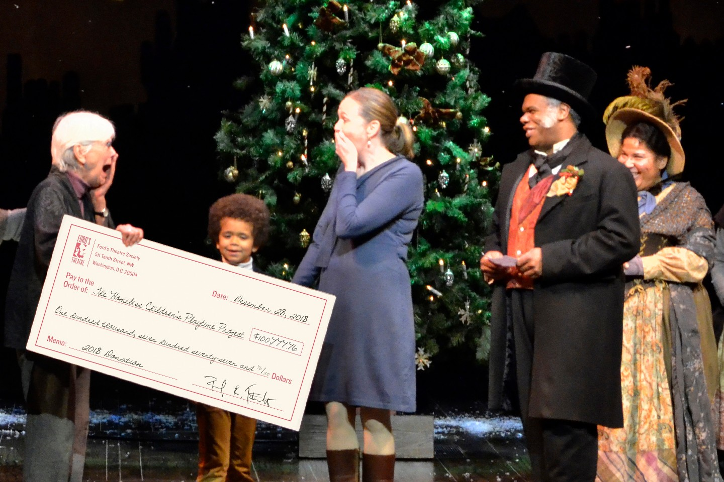 Onstage, two actors wearing Victoria-period clothes and top hats hand a large ceremonial check to two women wearing modern clothing.