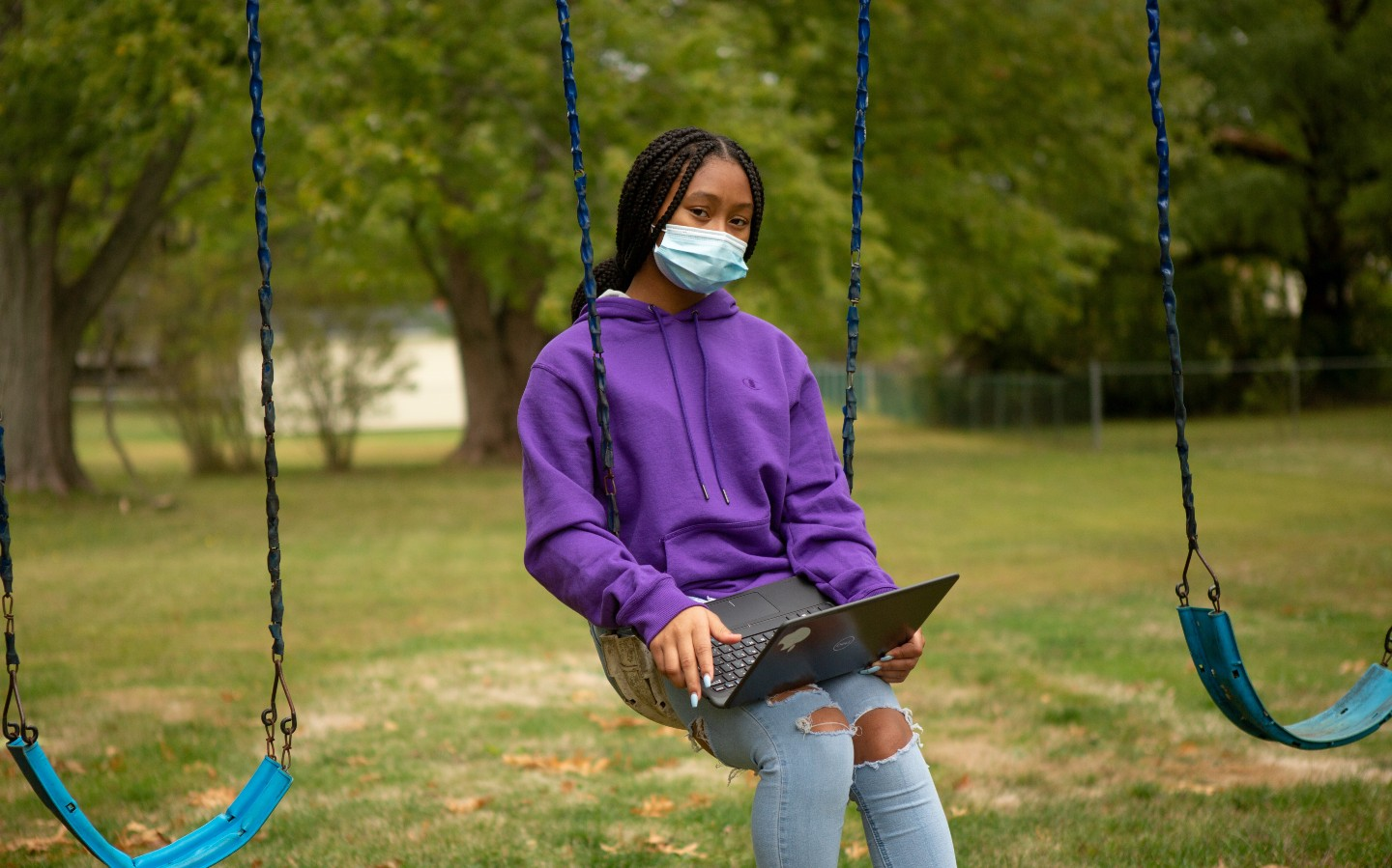A remote learning student works on an assignment on the swing set at her home.