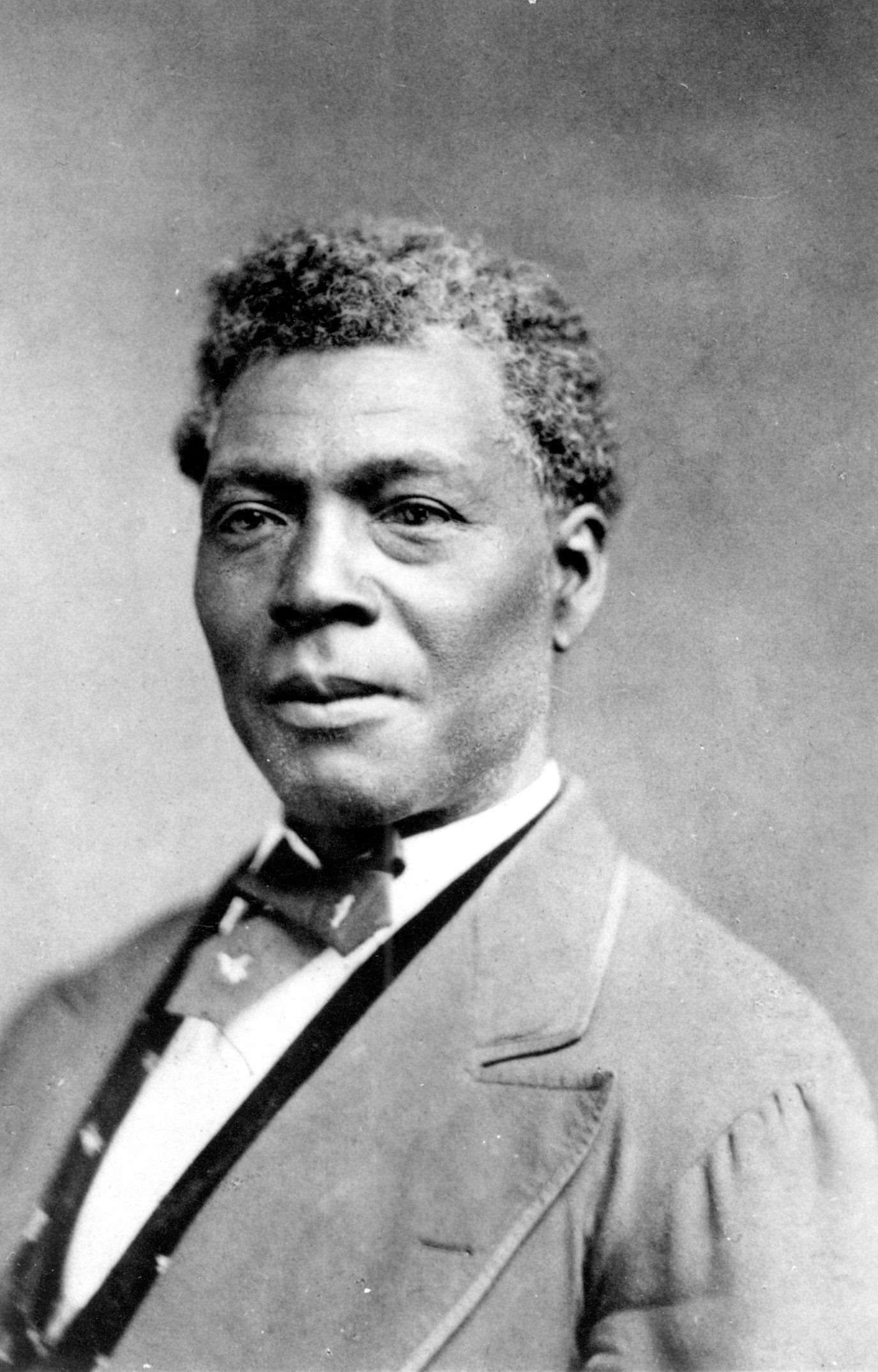 Photograph portrait of Archer Alexander, former slave. Photograph is a copy photo of an earlier work. Alexander is seen from chest up with body and head slightly angled toward the left. He is wearing a light colored jacket with pointed lapel, a dark vest, white shirt, and dark tie.