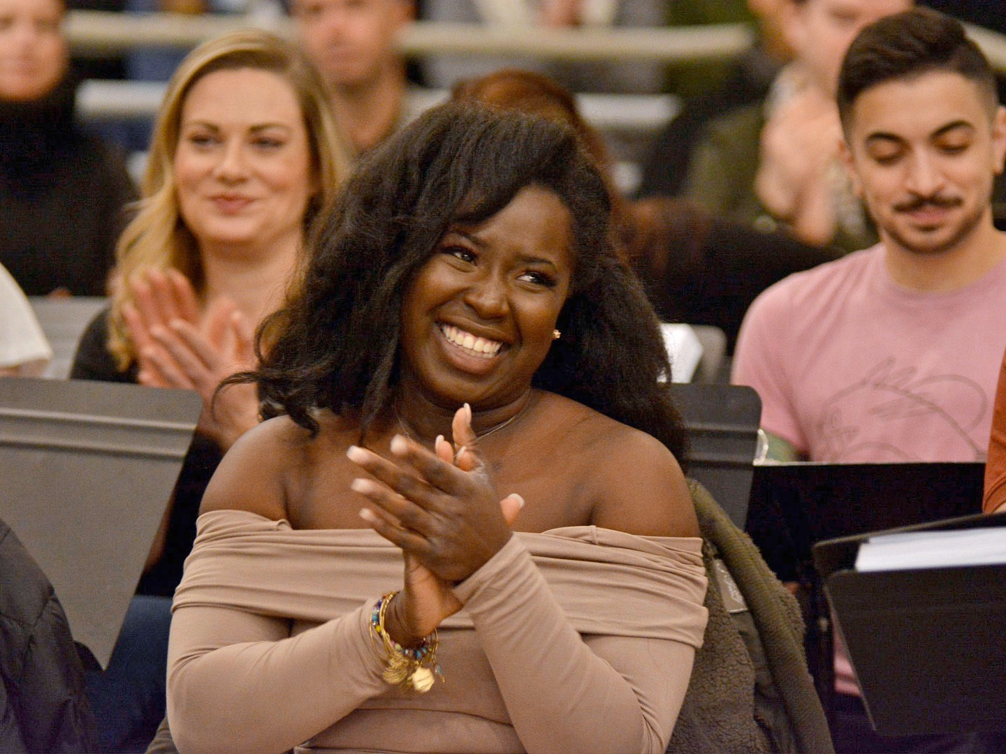 An African-American actress with shoulder-length hair claps while seated in a rehearsal room. She is wearing an off-the-shoulder, long sleeved tan dress and several gold charm bracelets