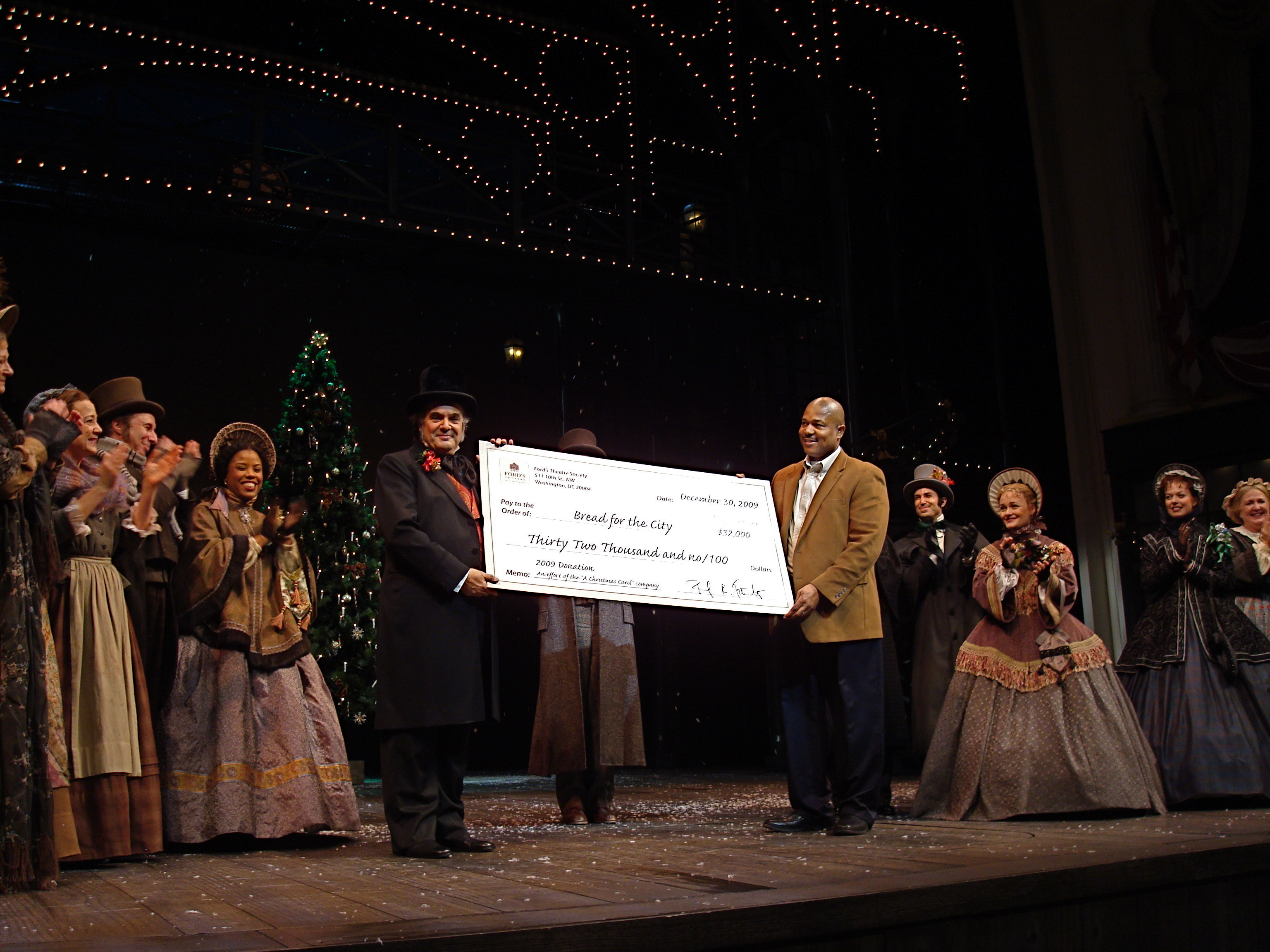 "The 2009 cast of ""A Christmas Carol"" at Ford's Theatre stand in costume on stage. Lead actor Edward Gero is shown presenting a giant check to Bread for the City for $32,000."