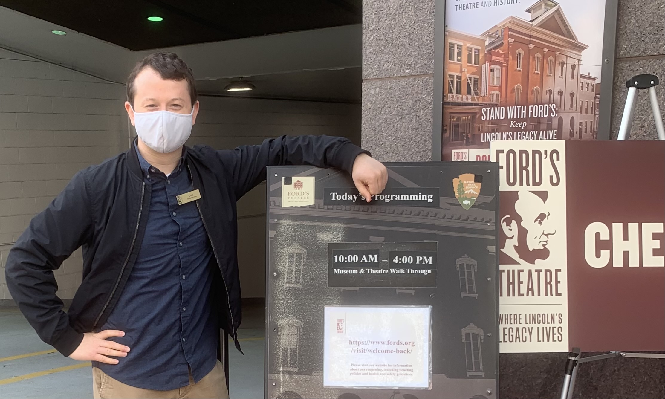 Chris stands outside of the Ford's Theatre entrance with the board where daytime entry details are posted.