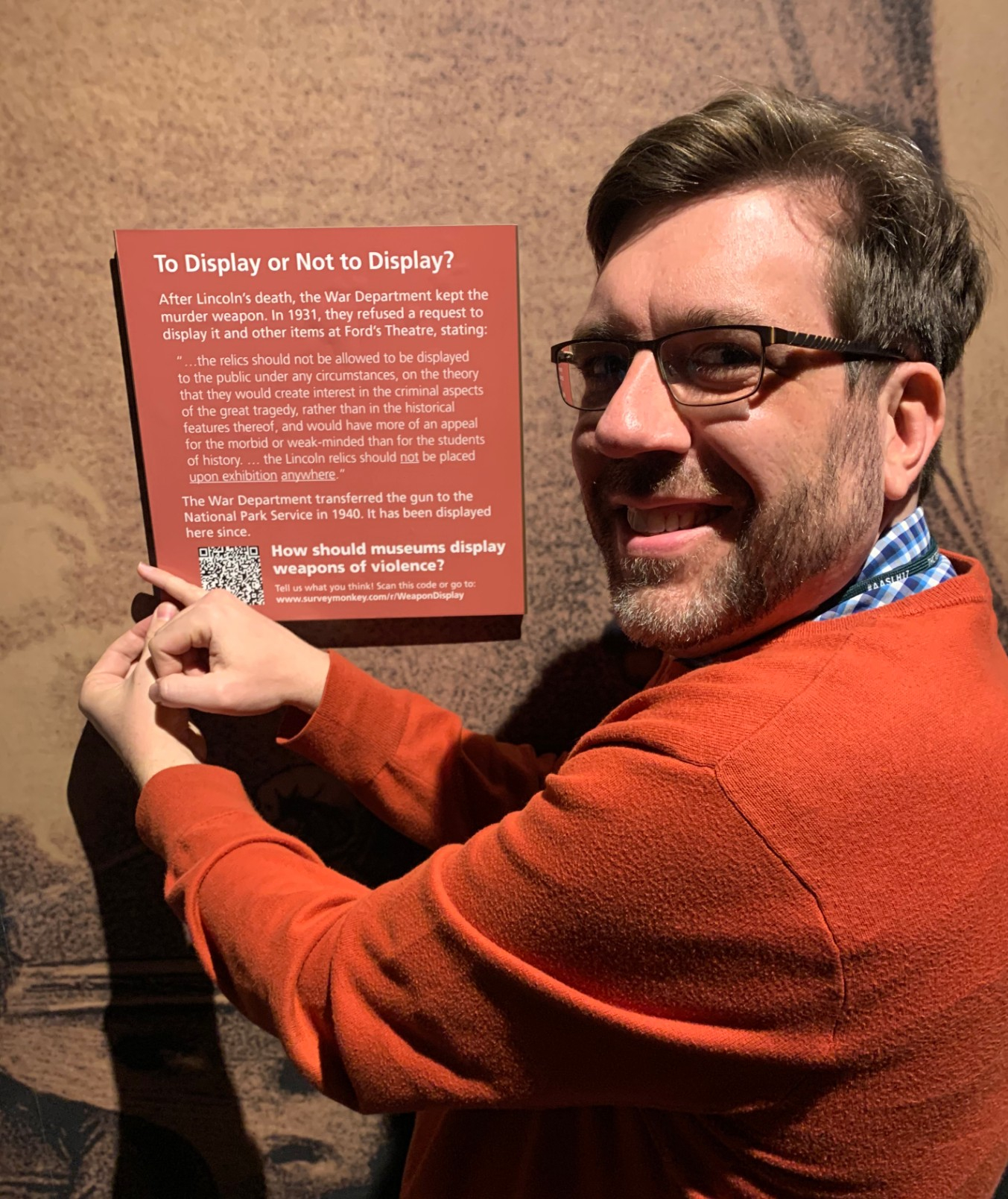 "Man smiles while hanging a square orange sign on the Ford's Theatre Museum wall. The sign reads ""To display or not to display?"" with information about the National Park Service's acquisition of John Wilkes Booth's pistol."