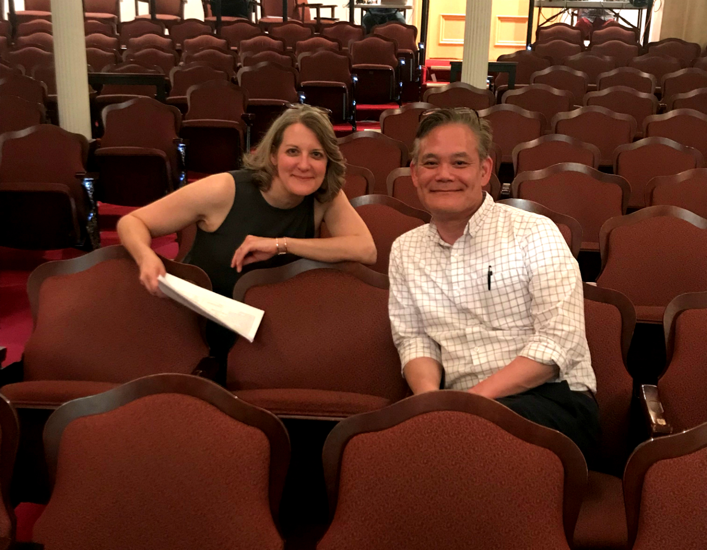 Diane Nutting and Roger Ideishi sit inside of Ford's Theatre in the orchestra section. Roger is an Asian-American man and Diane is a white woman with shoulder-length blonde hair.