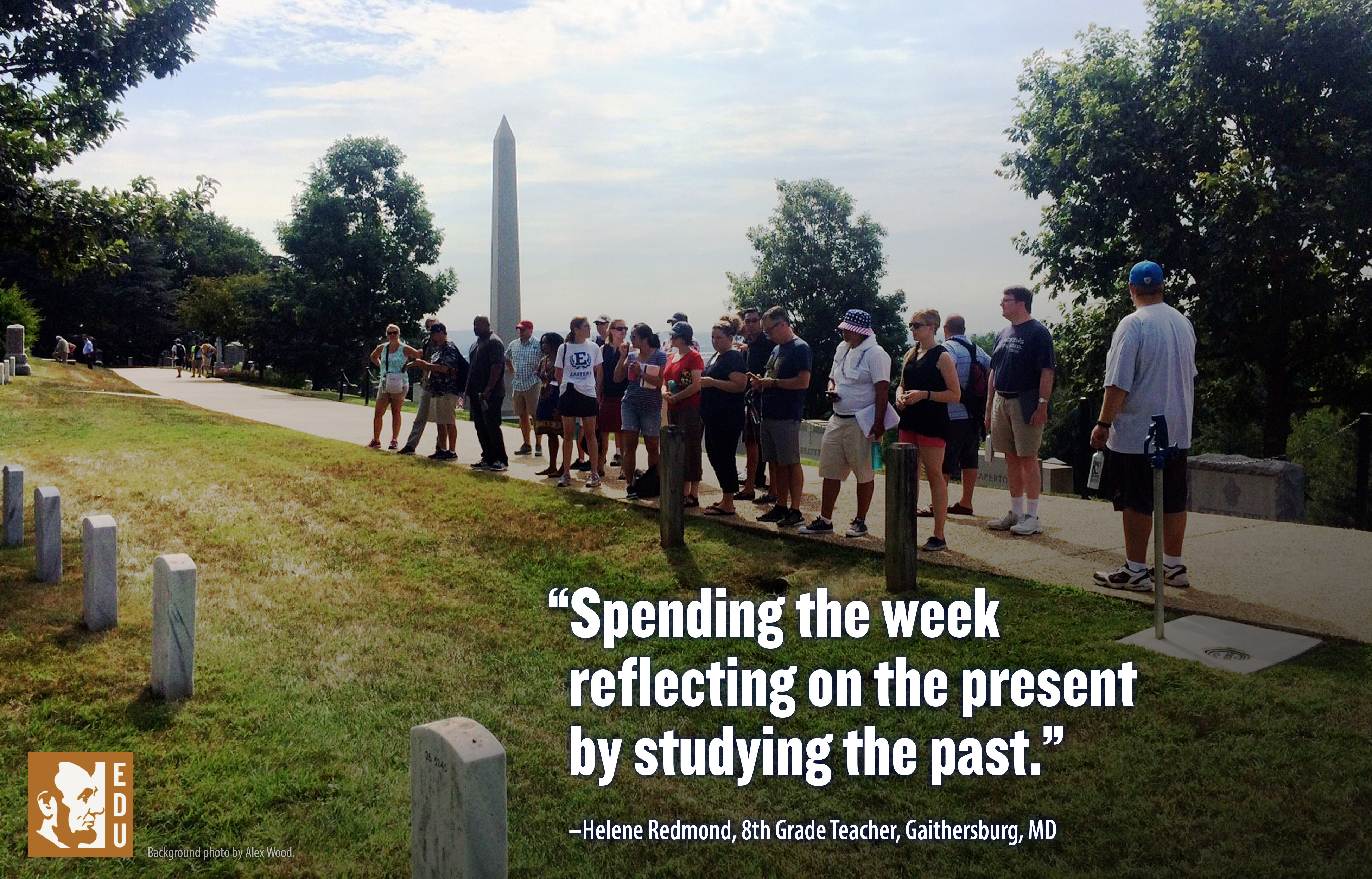 A group of teachers stand at Arlington National Cemetery. Behind them in the distance, the Washington Monument is seen.