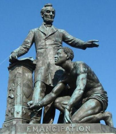 Statue in a park features President Abraham Lincoln with the Emancipation Proclamation in his right hand and holding his left hand over the head of a liberated slave kneeling at his feet.