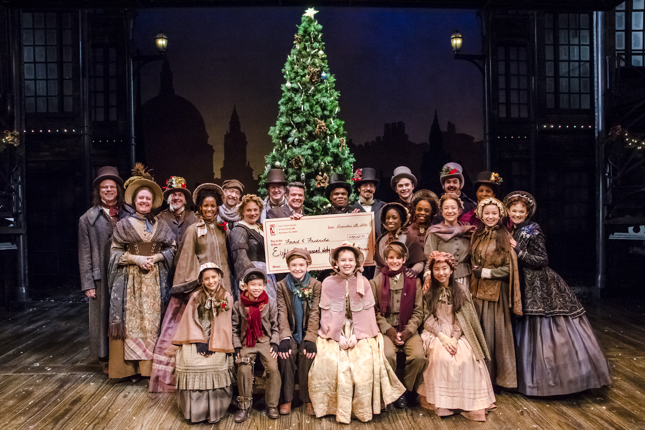 "The 2016 cast of ""A Christmas Carol"" stand on stage in costume with staff from Food & Friends and a giant check for more than $88,000."