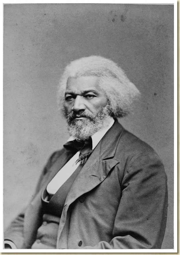 Black-and-white photograph of Frederick Douglass in a three piece suit, and tie. Photographed from the waist up.